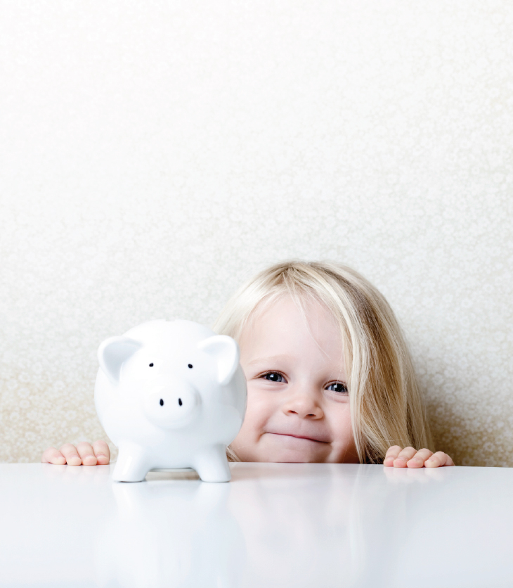 Young, happy girl standing with her piggy bank