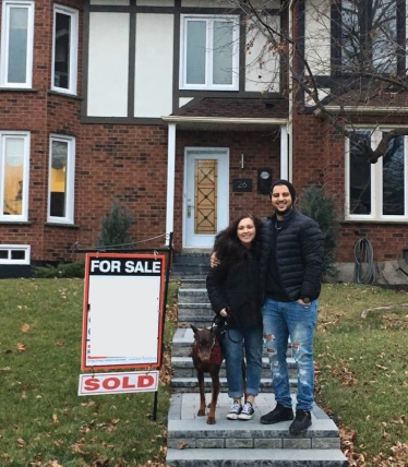 First Time Home Buyers in front of their new house